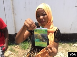 CCM supporter shows her candidate's photo on a campaign badge in Dar es Salaam, Oct. 24, 2015. (Jill Craig/VOA)