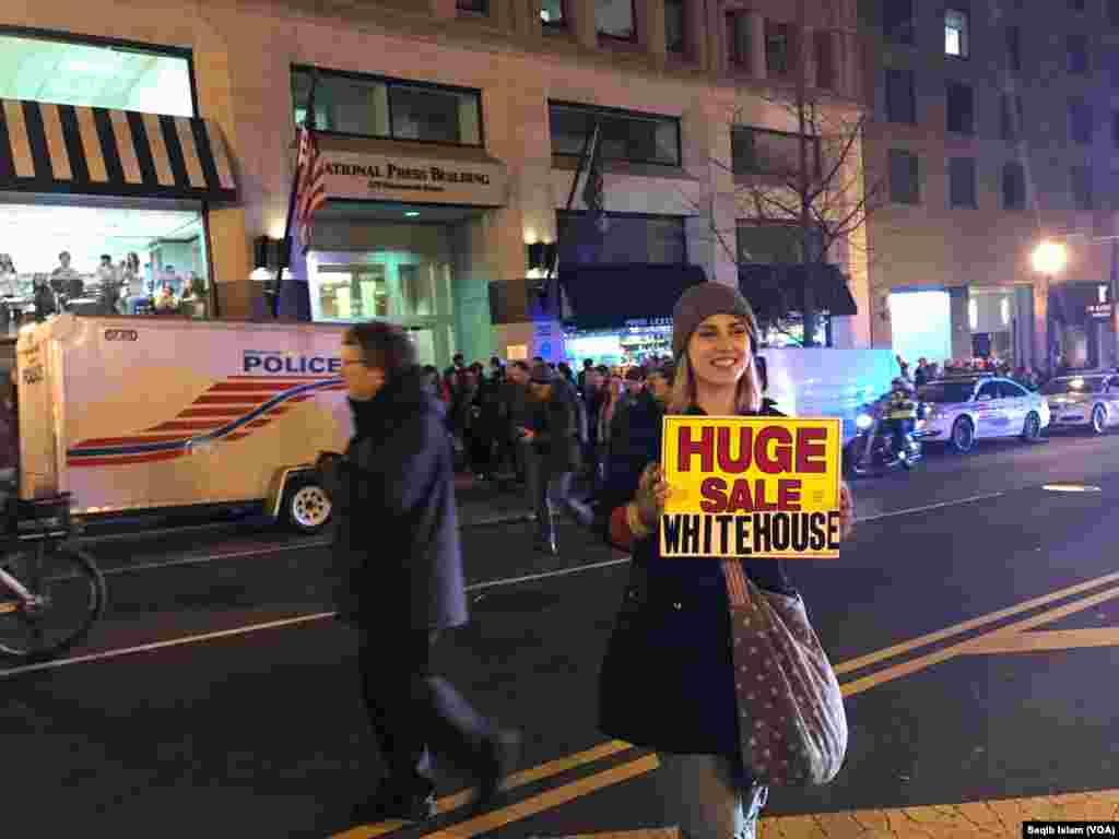 Une jeune femme tient un panneau avec une mention de protestation anti-Trump à l'extérieur du club national de la presse de Washington, 19 janvier 2017.