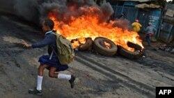 Une jeune écolière passe devant des barricades en feu à Kibera, Nairobi le 23 mai 2016.