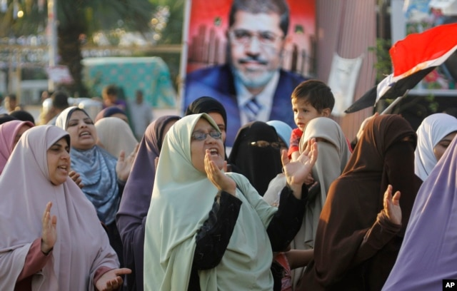 Supporters of Egypt's ousted president, Mohamed Morsi, shout slogans at a park in front of Cairo University, July 18, 2013.