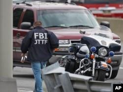 FILE - A law enforcement official wearing an FBI Joint Terrorism Task Force jacket works near the Pentagon, June 17, 2011, in Arlington, Va.