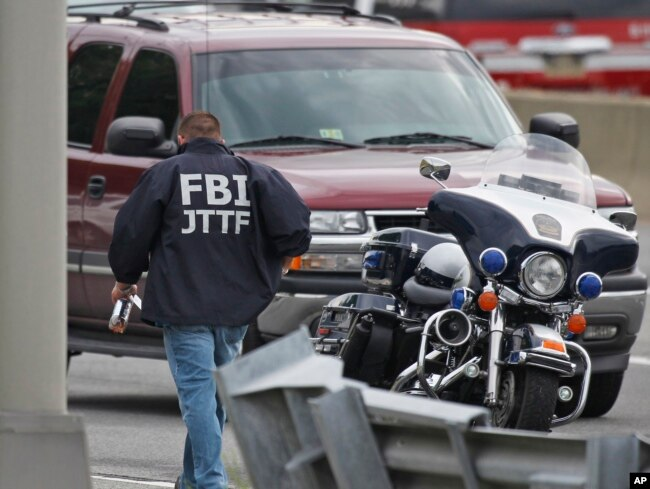 FILE - A law enforcement official wearing an FBI Joint Terrorism Task Force jacket works near the Pentagon, June 17, 2011, in Arlington, Va.