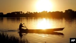 FILE - A fisherman rows a canoe on Lake Chad, in Koudouboul, Chad, Nov. 25, 2006.