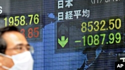 A man walks past a screen displaying stock prices in Tokyo, March 15, 2011