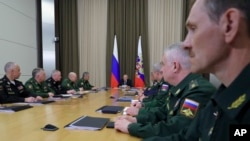 Russian President Vladimir Putin, background center, leads a meeting with the top military brass in the Bocharov Ruchei residence in the Black Sea resort of Sochi, Russia, May 15, 2018. Putin says the new weapons presented this year will ensure Russia's security for decades to come.