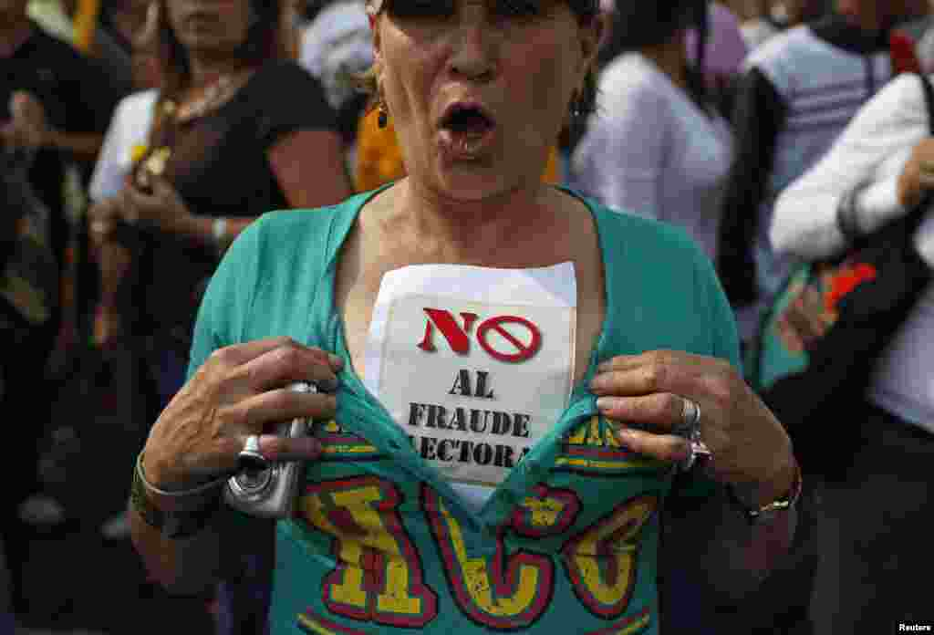 "A supporter of opposition leader Henrique Capriles wears a sign that reads, ""No election fraud,"" while demonstrating for a recount of the votes in Sunday's election, in Caracas, April 15, 2013."
