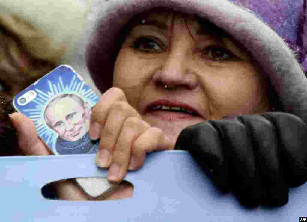 A woman holds a smartphone bearing an image of Russian President Vladimir Putin as Pro-Kremlin supporters march in central Moscow as they celebrate the National Unity Day.
