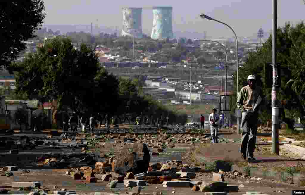 A man walks on a street filled with rocks and stones left behind by protesters who were dispersed by police in Soweto, South Africa.
