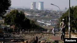 Un homme marche sur une rue jonchée de de pierres laissées par les manifestants dispersés par la police à Soweto, Afrique du Sud, 7 mai 2015. IMAGES REUTERS / Siphiwe Sibeko TPX DU JOUR