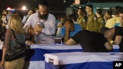 Relatives mourn over the coffins of people killed in a bombing in Bulgaria as the remains arrived back at an airport in Tel Aviv, Israel, Friday, July 20, 2012. A man carried out a deadly suicide attack on a bus full of Israeli vacationers on Wednesday i