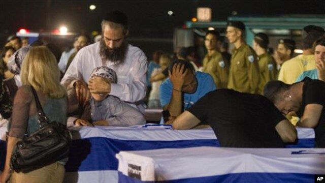 Relatives mourn over the coffins of people killed in a bombing in Bulgaria as the remains arrived back at an airport in Tel Aviv, Israel, July 20, 2012.