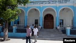 FILE - People walk outside Somalia's central Bank in Hamarwayne district, south of capital Mogadishu, May 16, 2013.