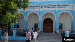 People walk outside Somalia's central Bank in Hamarwayne district, south of capital Mogadishu, May 16, 2013.