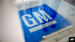 FILE - In this Thursday, Jan. 10, 2013 file photo, the logo for General Motors decorates the entrance to a former UPS facility as GM announced plans to open an information technology center in the building that would create about 1,000 jobs, in Roswell, G