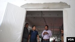 Managers at Alif Embroidery Village walk through a new fire door that was imported and meets international standards. (Amy Yee/VOA)