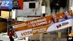 Un correligionario de Henrique Capriles coloca una manta de su candidato, mientras atrás aparece otra de su contincante, el presidente Hugo Chávez.