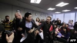 Du Jianguo adlı Çinli görevliler tarafından salondan çıkarılırken