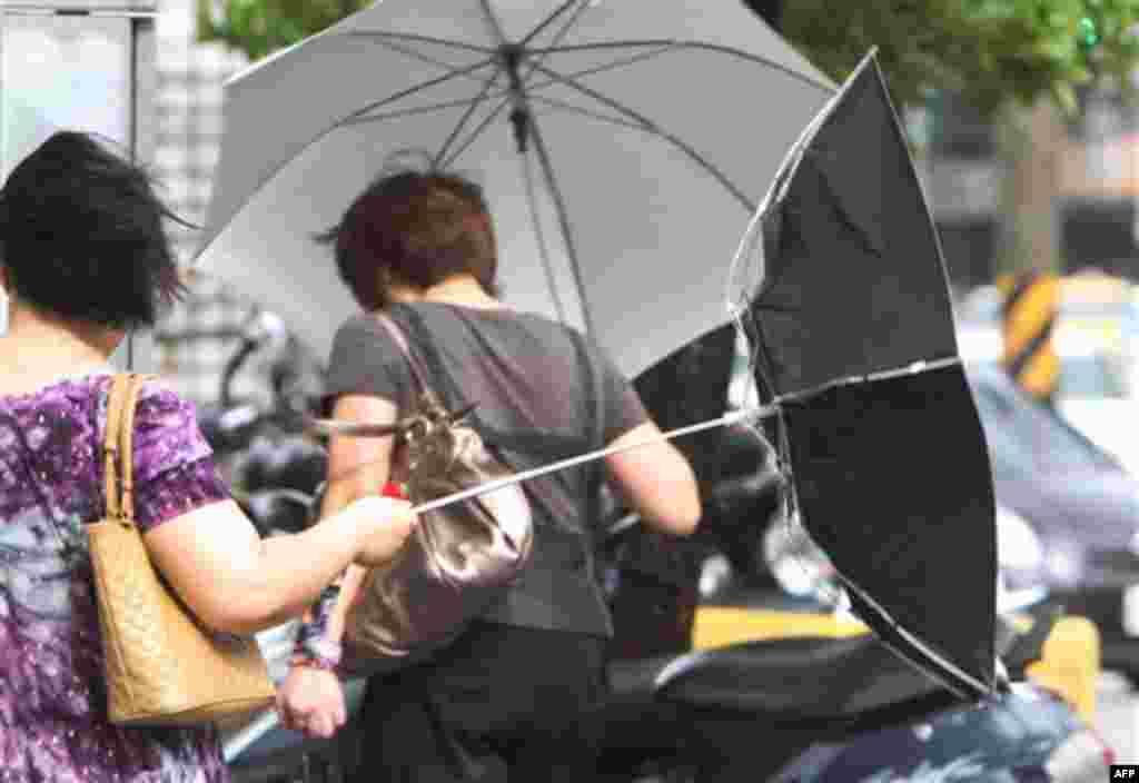 A woman with an umbrella is caught by powerful gusts of wind generated by typhoon Nanmadol in Taipei, Taiwan, Monday, Aug. 29, 2011. Typhoon Nanmadol has slammed into Taiwan, closing schools, workplaces and government offices. It has dumped more than 19 i