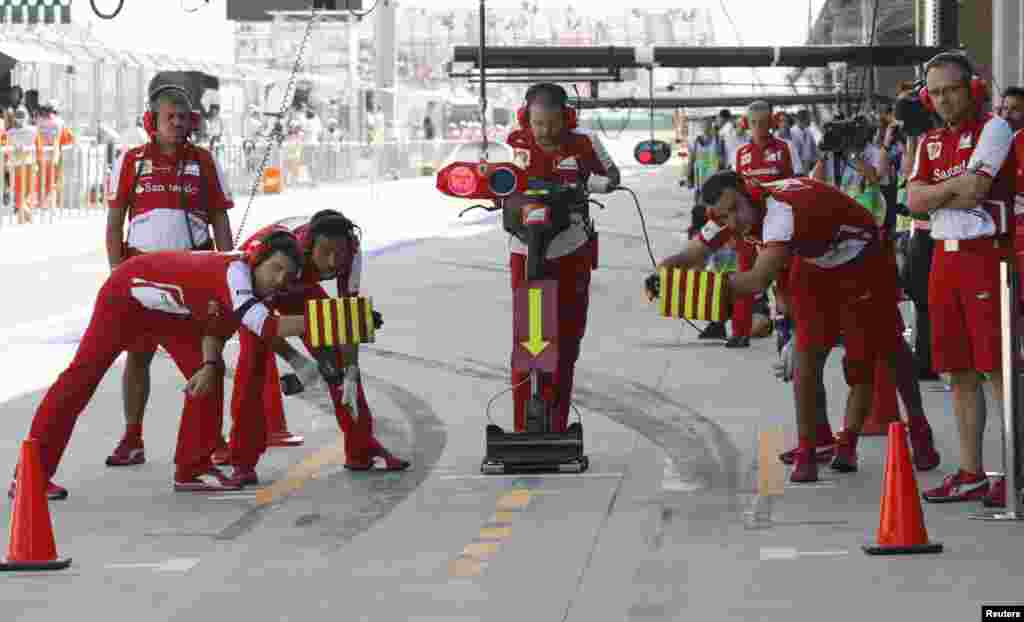 Pit crew wait for Ferrari Formula One driver Felipe Massa of Brazil during the third practice session of the Korean F1 Grand Prix at the Korea International Circuit in Yeongam, South Korea.