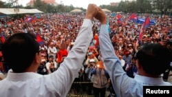 Pemimpin oposisi Kamboja Sam Rainsy (kiri) dan Kem Sokha memimpin protes menentang hasil pemilu Kamboja di Phnom Penh, Senin (16/12).