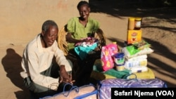 Lungisani and her father smile after receiving a donation of various goods.