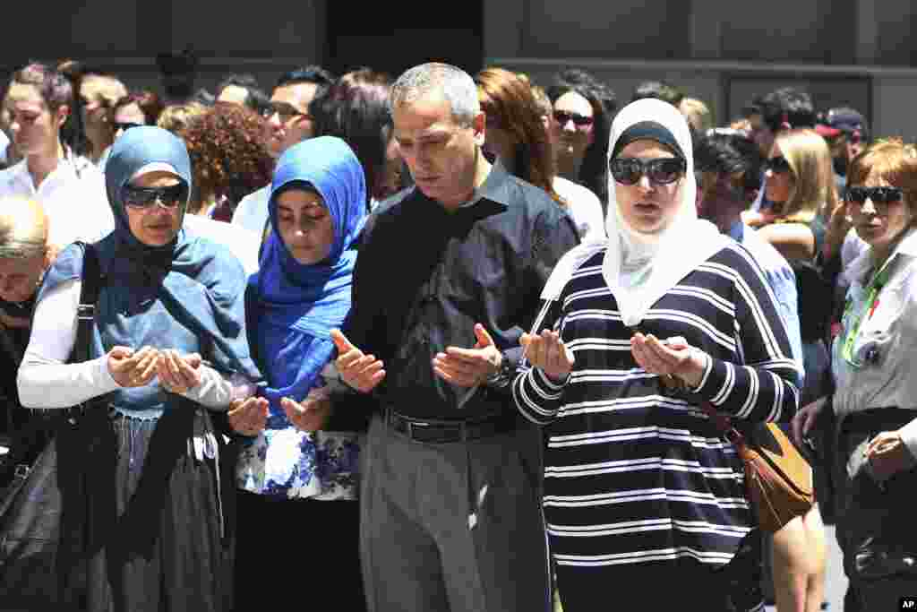 Sydney Muslim community leader Jamal Rifi, center, and his family members pray at a makeshift memorial after a siege at Martin Place in the central business district of Sydney, Australia Tuesday, Dec. 16, 2014.