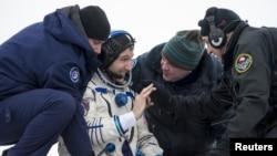 Astronot Michael Hopkins dari NASA ditolong keluar dari kapsul Soyuz setelah mendarat di Zhezkazgan, Kazakhstan (11/3).