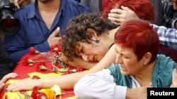Keluarga Korkmaz Tedik, korban yang tewas dalam ledakan bom hari Sabtu berduka di peti matinya saat pemakaman di Ankara, Turki, 11 Oktober 2015.