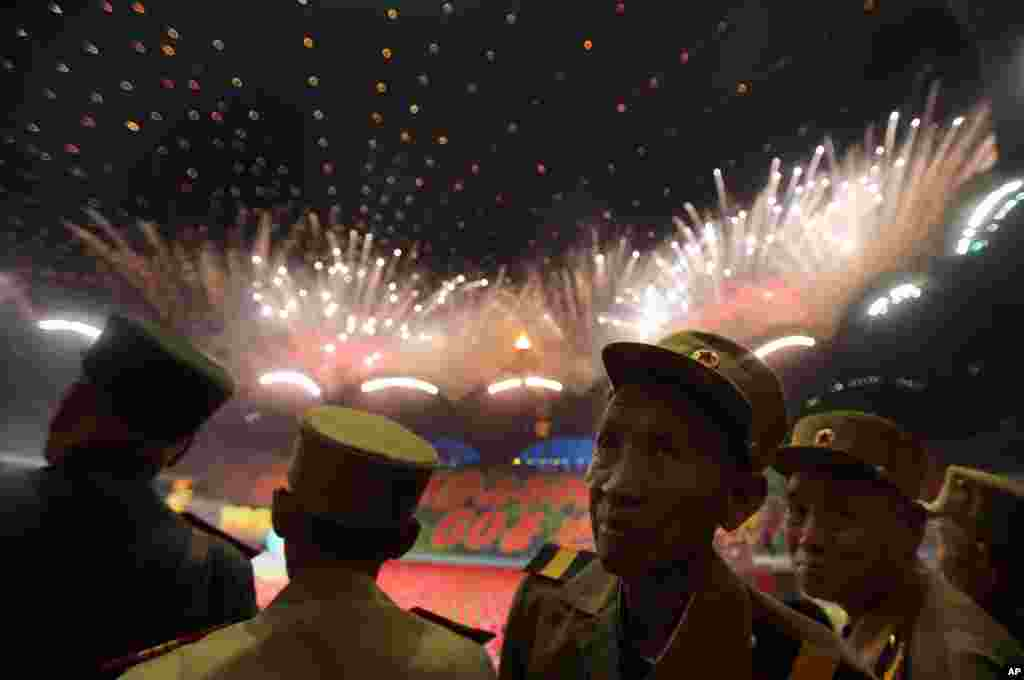 "North Korean war veterans of the Korean War watch fireworks during the ""Arirang"" mass games song-and-dance ensemble on the eve of the 60th anniversary of the Korean War armistice in Pyongyang."