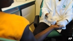 Un agent de santé bénévole prélève du sang sur un patient pour un test de dépistage du VIH-SIDA, à Noe, une ville en Côte d'Ivoire près de la frontière du Ghana, 18 juin 2008.
