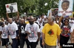 Michael Brown Sr., center, leads a memorial march for his son, Michael Brown, in Ferguson, Missouri, Aug. 8, 2015.