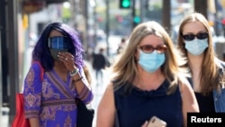 People wearing face protective masks walk on Hollywood Blvd during the outbreak of the coronavirus disease (COVID-19), in Los Angeles, California, U.S., March 29, 2021.