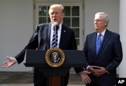 President Donald Trump answers questions with Senate Majority Leader Mitch McConnell, R-Ky., in the Rose Garden at the White House, Oct. 16, 2017.
