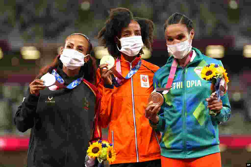 Gold medalist Sifan Hassan, of Netherlands, center, stands with silver medalist Kalkidan Gezahegne, of Bahrain, left, and bronze medalist Letesenbet Gidey, of Ethiopia, during the medal ceremony for the women's 10,000-meters at the 2020 Summer Olympics, Saturday, Aug. 7, 2021, in Tokyo. (AP Photo/Martin Meissner)