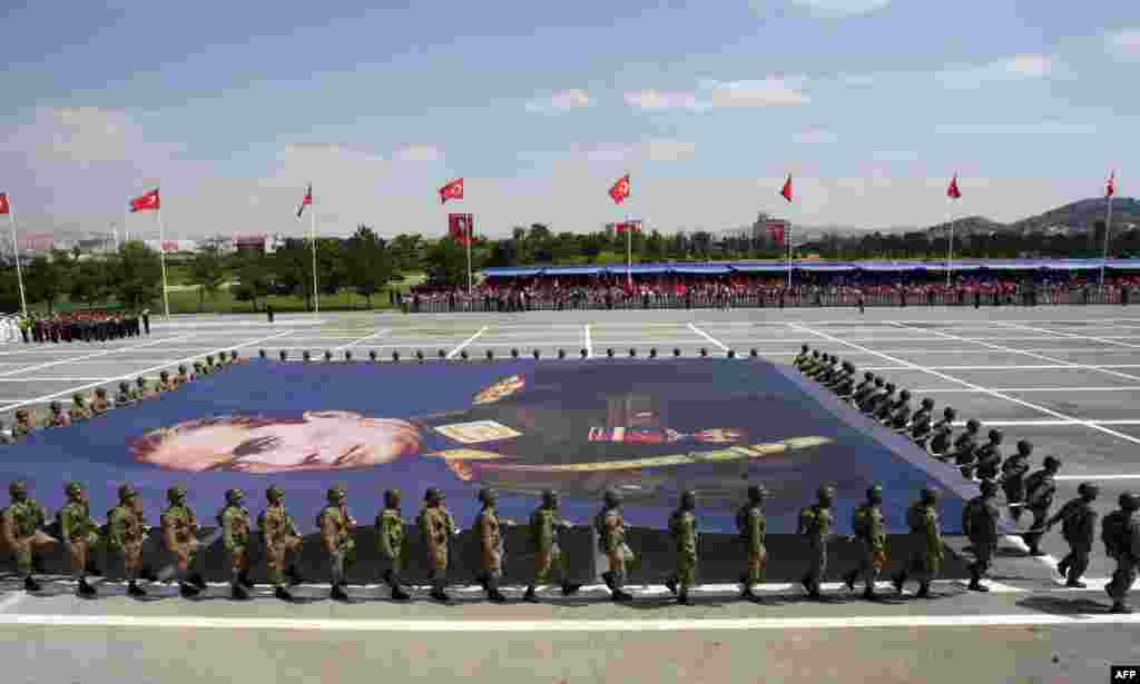 Turkish soldiers carry a giant banner bearing a portrait of Mustafa Kemal Ataturk, founder of modern Turkey, during a parade marking the 91st anniversary of Victory Day in Ankara.