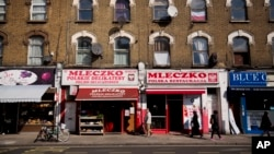 FILE - People walk past the Polish Mleczko delicatessen and restaurant in London, April 5, 2016. Following right-wing election gains, Eurosceptics in Austria and Poland are keeping a close eye on Britain's June 23rd referendum to stay or quit the European Union.