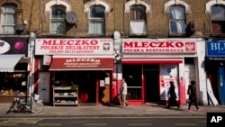 FILE - People walk past the Polish Mleczko delicatessen and restaurant in London, April 5, 2016. Following right-wing election gains, Eurosceptics in Austria and Poland are keeping a close eye on Britain's June 23rd referendum to stay or quit the European