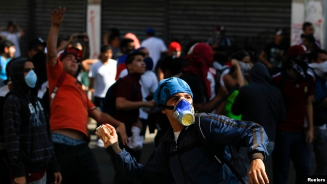 Opposition demonstrators throw stones at police during a protest against Venezuela's President Nicolas Maduro's government in Caracas, Feb. 12, 2014.