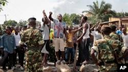 Des manifestants opposés à la candidature du président Pierre Nkurunziza font face aux militaires, le 27 mai 2015.