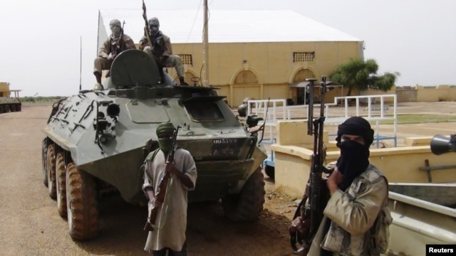 Fighters from the Al Qaeda-linked Islamist group MUJWA, who are traveling with a convoy including Burkina Faso Foreign Minister Djibril Bassole, stand guard in Gao, northern Mali, August 7, 2012.