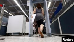 FILE - A passenger walks through an airport security checkpoint.