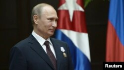 Russia's President Vladimir Putin looks on after Cuba's President Raul Castro decorated him with the Order of Jose Marti during a ceremony at Havana's Revolution Palace, July 11, 2014.