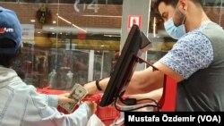 13 Ocak 2020 - Venezuela'nın başkenti Caracas'ta bir müşteri dolarla alışveriş yaparken