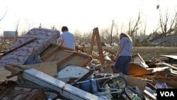 Warga berjalan di antara reruntuhan rumahnya setelah terjadinya tornado di Harrisburg, Illinois. Tornado menghantam beberapa kawasan di Amerika tenggara.