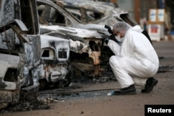 A French police officer photographs burned vehicles outside the Splendid Hotel in Ouagadougou, Burkina Faso, Jan. 17, 2016.