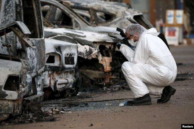A French police officer photographs burned vehicles outside the Splendid Hotel in Ouagadougou, Burkina Faso, Jan. 17, 2016.