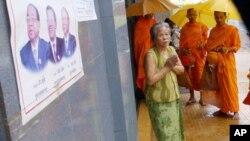 A Cambodian People's Party poster hangs on a wall outside a business as a woman offers prayers to Buddhist Monks.
