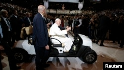 Pope Francis is driven on a golf cart as he arrives at Madison Square Garden to celebrate mass in New York, Sept. 25, 2015.