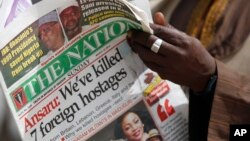 A man reads a local newspapers with the headline 'We've killed 7 foreign hostages' on a street in Kano, Nigeria, Sunday, Mar. 10, 2013.