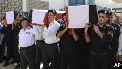 Des policiers portant les corps de leurs collègues qui, selon le gouvernement, ont été tués dans des affrontements avec des hommes armés